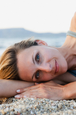 Closeup portrait of mid-aged woman laying on a beach (for Vampire Facelift with Selphyl procedure)